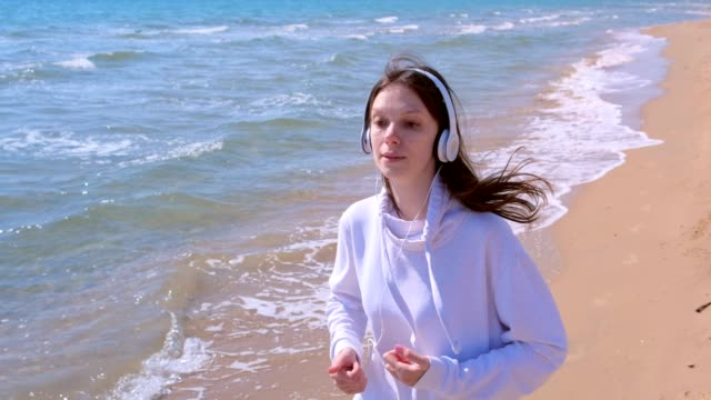 Girl in headphones music jogging at sea sand beach sport run outdoor training.