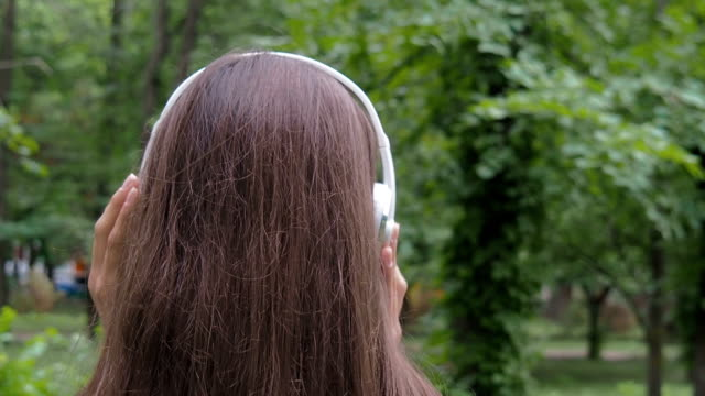 Girl in headphones on nature. Girl in headphones on nature. Beautiful girl puts on headphones. bluetooth stock videos & royalty-free footage
