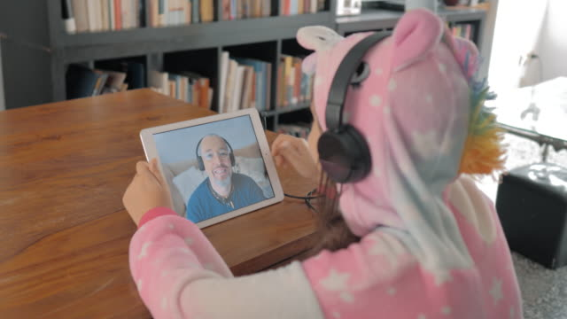girl in hood pajamas in conversation with quarantine family hearing aids on tablet