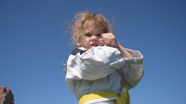 kimono kız dışarı darbeler yerine getirir - karate stok videoları ve detay görüntü çekimi