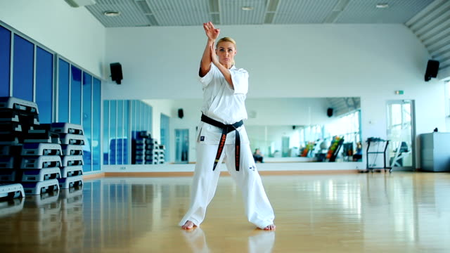 Girl in kimono with black belt show some karate tricks ビデオ
