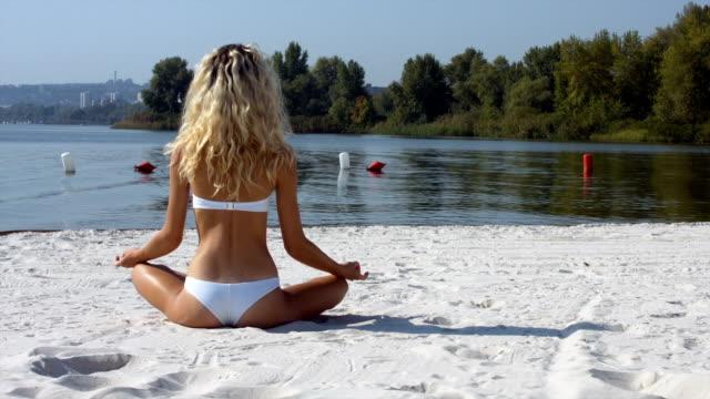 flicka i lotusställning på stranden - korslagda ben bildbanksvideor och videomaterial från bakom kulisserna