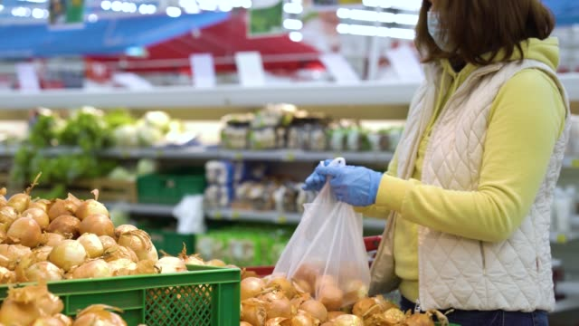 Girl in mask buying onions at grocery store video