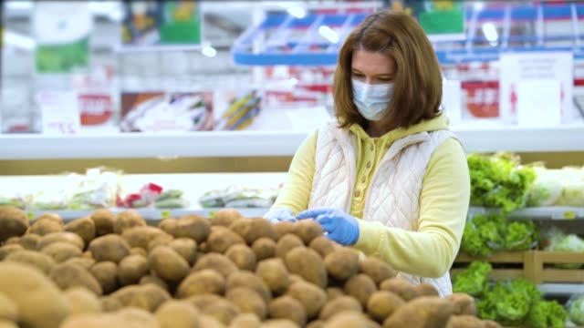 Girl in mask picking potatoes in vegetable department at grocery store video