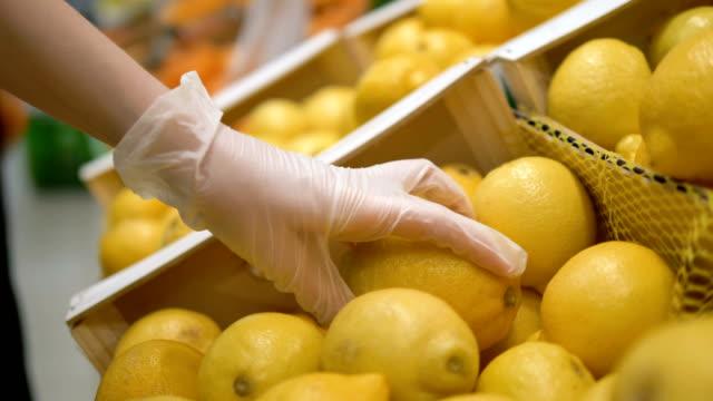 vídeos y material grabado en eventos de stock de chica con guantes médicos elige limón en un supermercado. cocronovirus de protección personal, vitamina c - guante quirúrgico