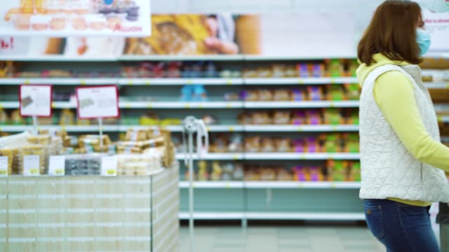 Girl in medical mask and gloves passing by with shopping cart in supermarket video
