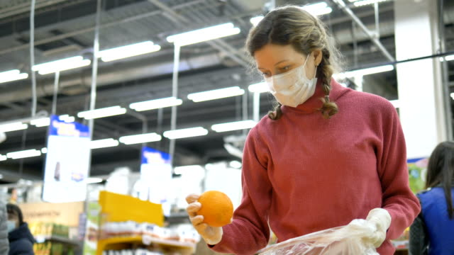 girl in medical mask and rubber gloves carefully selects oranges, increasing immunity vitamin C - vídeo