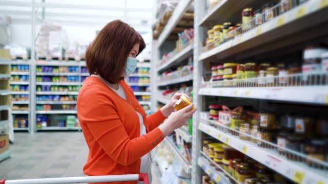 Girl in medical mask buying honey in supermarket during COVID video