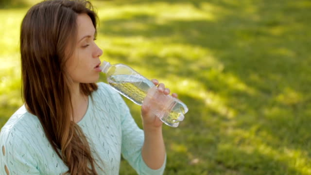 A girl in nature drinking water from a plastic bottle video
