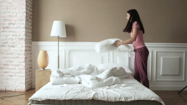 flicka i pyjamas tucks sängkläder tidigt på morgonen i sitt sovrum. - duntäcke bildbanksvideor och videomaterial från bakom kulisserna