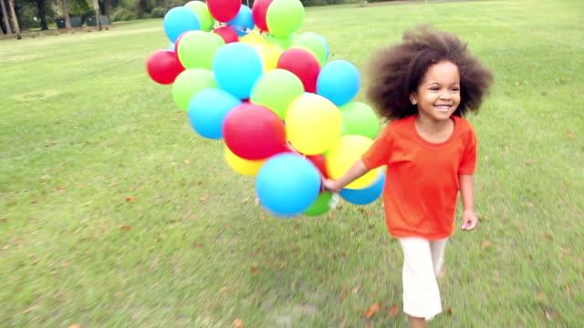カラフルな風船の大きな束で実行されている公園の少女 - 4歳から5歳点の映像素材/bロール