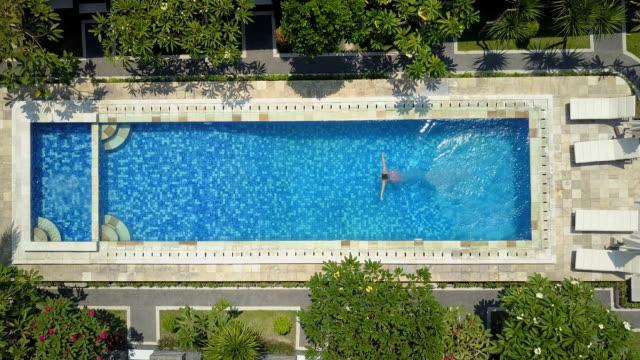 vídeos y material grabado en eventos de stock de antena lenta chica en bikini rosa saltando y nadando en la piscina vacía - backyard pool