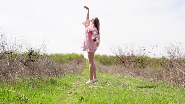 girl in pink dress posing in the garden video