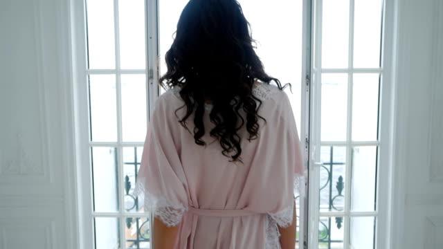 fille en robe rose en soie légère va sur le balcon - Vidéo
