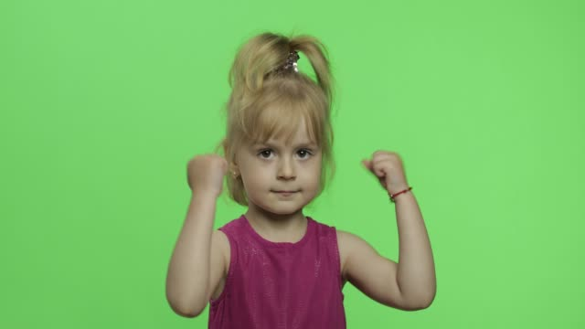 Girl in purple dress angry and shows fists. Four years old child. Chroma Key