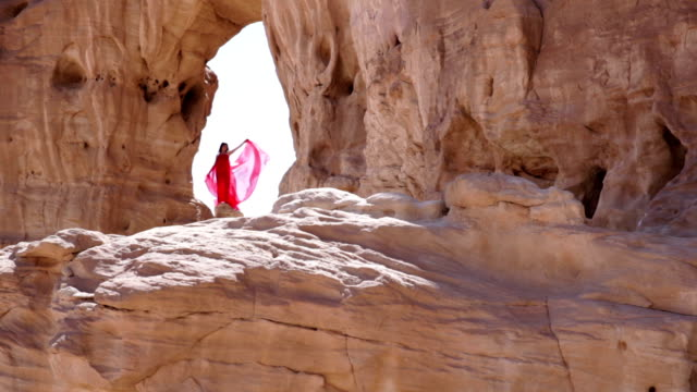 Girl in red dress standing on a rock video