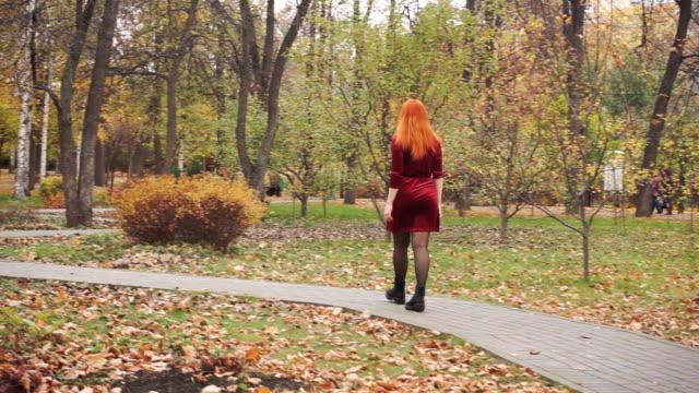 vídeos de stock, filmes e b-roll de garota de vestido vermelho anda na calçada e olha em volta - setembro amarelo