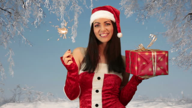 girl in red santa hat holding Christmas Present video