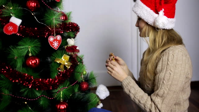 サンタの帽子の女の子を飾るクリスマス ツリー - サンタの帽子点の映像素材/bロール
