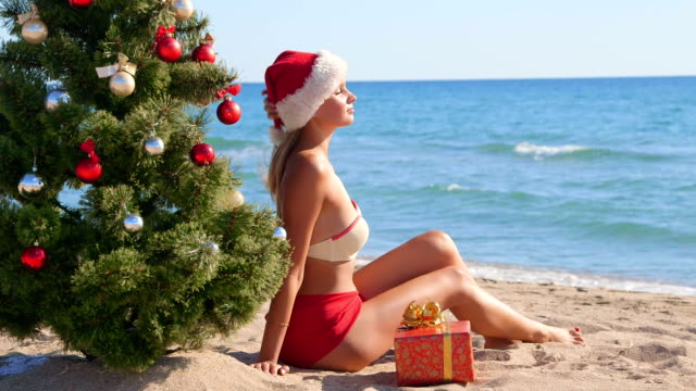 Girl in Santa hat enjoying Christmas vacation on beach video