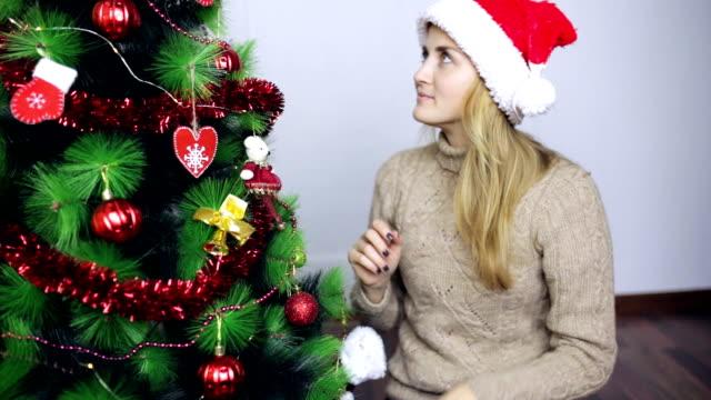 サンタさんの帽子の女の子がクリスマス ツリーを飾る - サンタの帽子点の映像素材/bロール