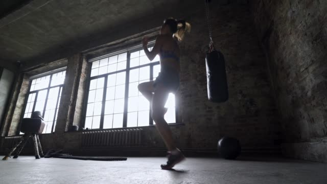 Girl in silhouette doing exercises and warming in gym
