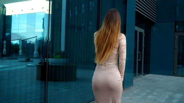 flicka i kjol med vackra rumpa och långt hår går runt staden och samtal på en mobiltelefon - bum bildbanksvideor och videomaterial från bakom kulisserna