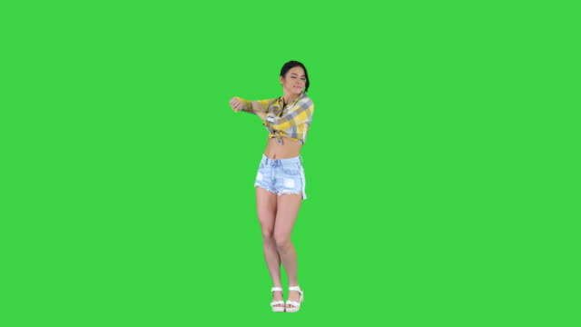 girl in square shirt and jeans shorts, sneakers, dancing on a green screen, chroma key - pantaloncini video stock e b–roll
