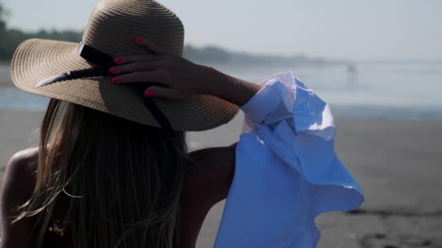 vídeos y material grabado en eventos de stock de chica con sombrero de verano caminando en la playa - disquete