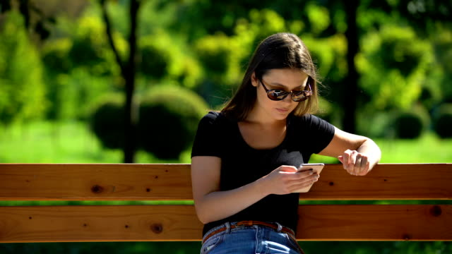 Girl in sunglasses scrolling smartphone resting on bench in sunny park, relax