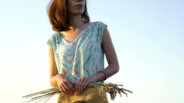 girl in sunglasses stands in a field at sunset and holding golden wheat spikes and straw hat. Rustic outdoor scene in golden tones video