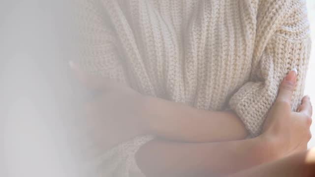 Girl in sweater and bare feet sitting on window,CU video