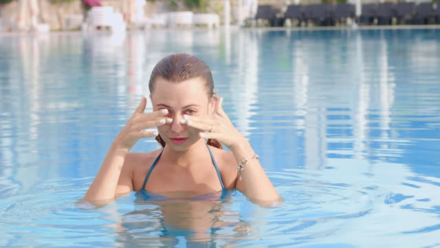 vídeos de stock e filmes b-roll de girl in swimming pool rubs her eyes, which the water hits - contacts