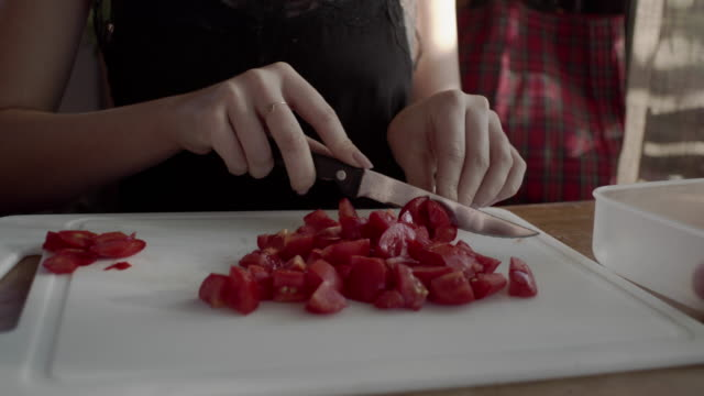 Girl in the kitchen cuts tomatoes