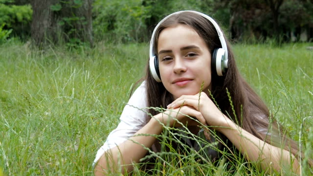 A girl in the nature listens to music. A girl in the nature listens to music. Beautiful girl in headphones lies on green grass. bluetooth stock videos & royalty-free footage