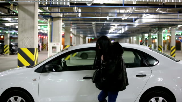 Girl in the underground garage sits in the car video