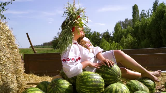 girl in traditional slavic costume sitting in trailer with watermelons outside - славянская культура стоковые видео и кадры b-roll