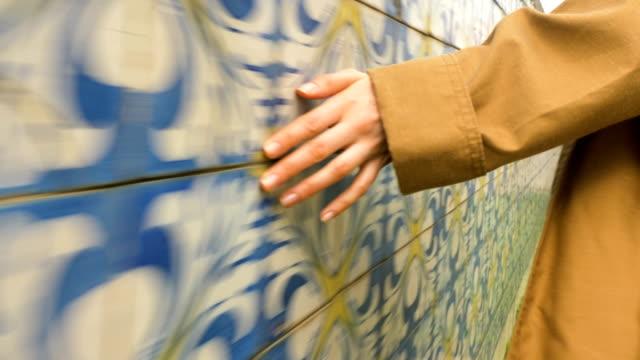 vídeos de stock e filmes b-roll de girl in trench coat runs hand over tile in lisbon portugal, slow motion - portugal