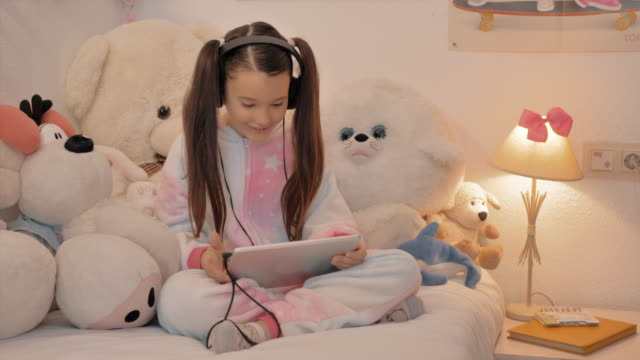 girl in unicorn pajamas sitting in her room talks happy with hearing aids in conference