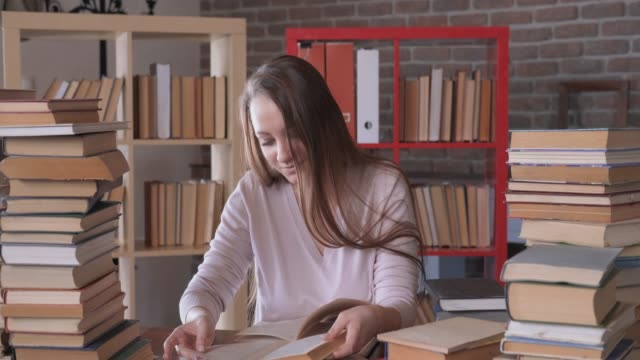 Girl in university library is diligently engaged in self-education, reads books, turns pages, studies, straightens hair, removes hair from eyes, compares what she read from different books, passion