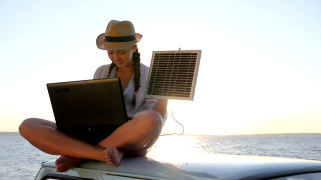 girl in vacation sits on roof car with solar array charges laptop in backlight, female sitting on vintage car with computer video