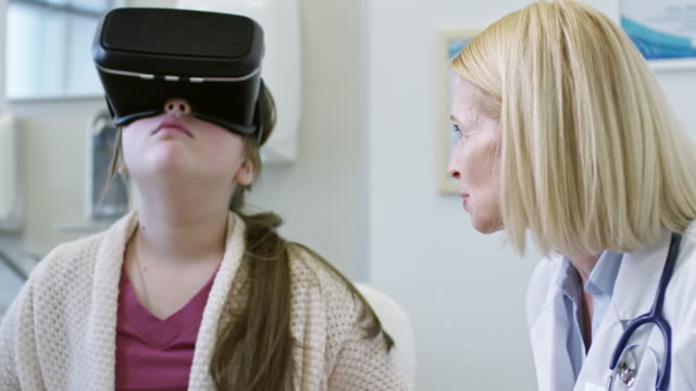 Girl in VR Headset on Dietician Appointment Tilt up of cheerful female dietician in lab coat talking to schoolgirl in VR headset and explaining her healthier food choices during consultation nutritionist stock videos & royalty-free footage