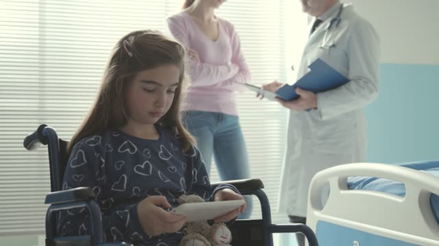 Girl in wheelchair using a digital tablet at the hospital Cute girl in wheelchair using a digital tablet at the hospital, her mother and the doctor are talking in the background persons with disabilities stock videos & royalty-free footage