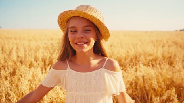 flicka i vit klänning och stråhatt tittar på vete fält - endast flickor bildbanksvideor och videomaterial från bakom kulisserna