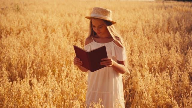 flicka i vit klänning och stråhatt läsning bok i vete fält - endast flickor bildbanksvideor och videomaterial från bakom kulisserna