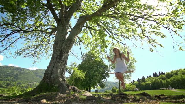 Girl in white dress swinging on rope swing under tree video