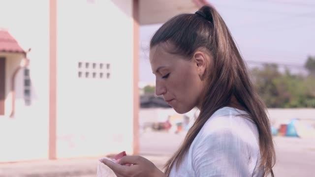 girl in white shirt eats watermelon slice against building