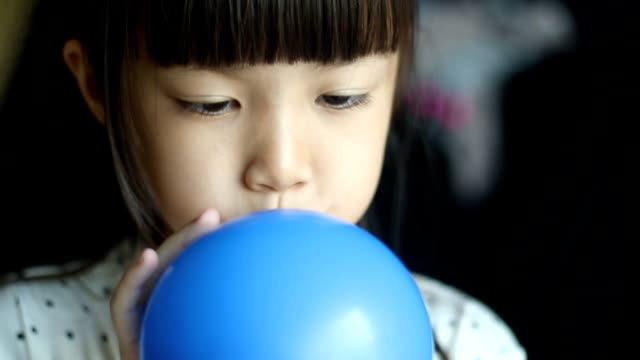 Girl inflating a blue balloon video
