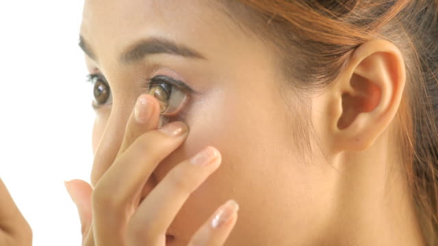 vídeos de stock e filmes b-roll de menina inserir lente de contacto no seu olho - contacts