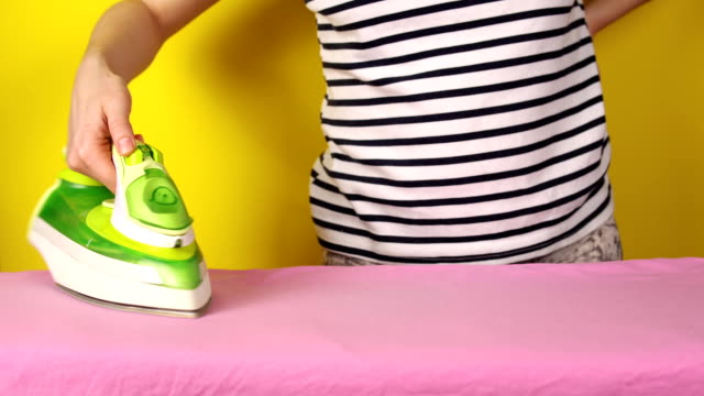 Girl irons bed linen on a yellow background video